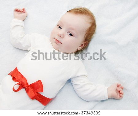 Adorable baby boy in light with red ribbon as gift