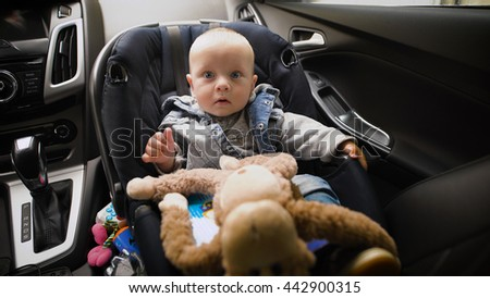 Adorable baby boy in safety car seat. He looks at the world with his huge blue eyes, around the toys. - stock photo