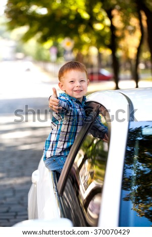 Adorable baby boy in the car non-moving car, showing unsafety