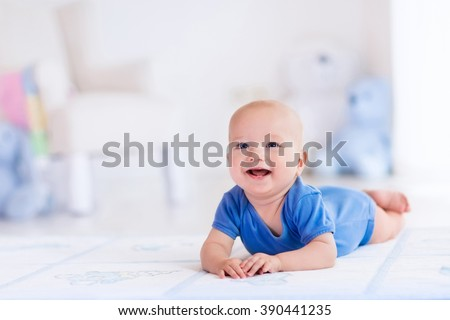 Adorable baby boy in white sunny bedroom. Newborn child relaxing on a rug. Nursery for young children. Furniture, textile and bedding for kids. New born kid during tummy time with toys at a window. - stock photo