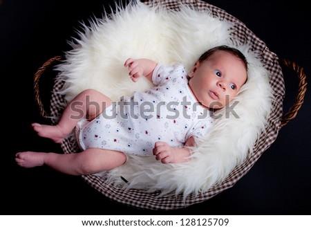 adorable baby boy in wicker basket - stock photo