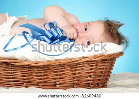 Adorable baby boy in wicker basket with blue bow