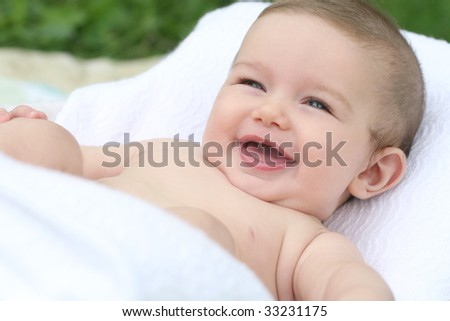 Adorable baby boy laughing; in white blankets - stock photo