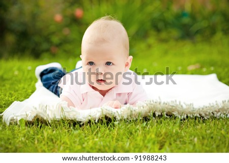 Adorable baby boy laying on grass in spring flowery garden. Shallow depth of fields - stock photo