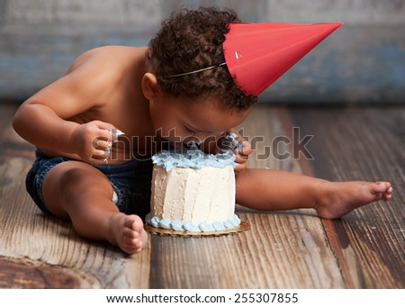 Adorable baby boy licking his birthday cake.
