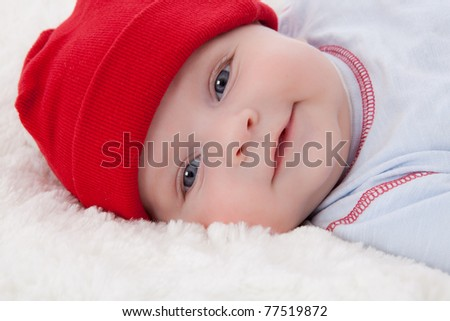 Adorable baby boy lying on soft fur blanket and cushion, smiling with red hat on - stock photo