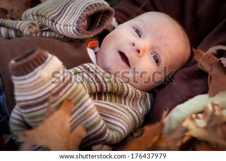 Adorable baby boy newborn surrounded by fall leaves - stock photo
