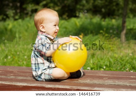 Adorable baby boy playing with a yellow beach ball outdoors - stock photo