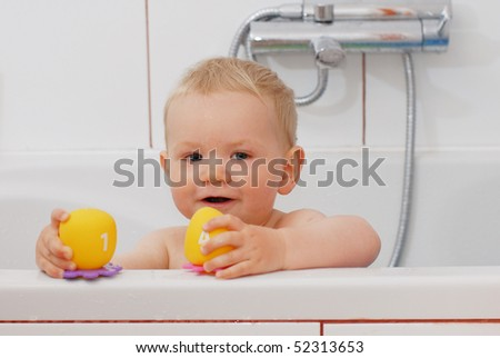 Adorable baby boy playing with toys while bathing