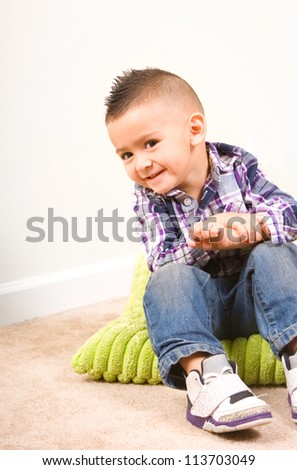 adorable baby boy portrait sitting on a pillow - stock photo