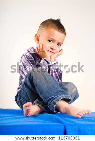 adorable baby boy portrait sitting with his hands under his chin