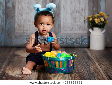Adorable baby boy sitting on a rustic wood floor, playing with an Easter Basket full of plastic eggs and wearing blue bunny ears.   - stock photo
