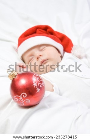 Adorable baby boy sleeping in christmas hat with a red Christmas ball on white blanket  - stock photo
