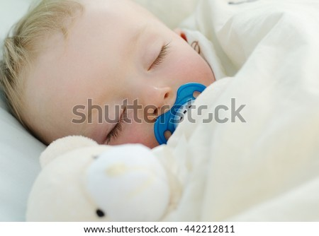 Adorable baby boy sleeping with a blue pacifier and teddy bear. Child concept.