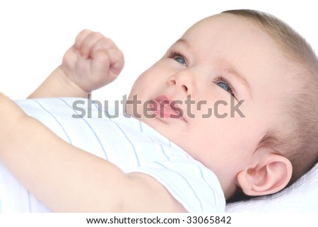 Adorable baby boy smiling, in white blankets - stock photo