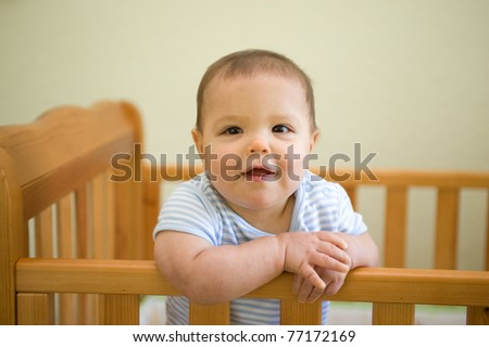 Adorable baby boy smiling standing up in his crib in the nursery - stock photo