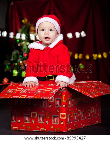 Adorable baby boy standing in large Christmas present box - stock photo