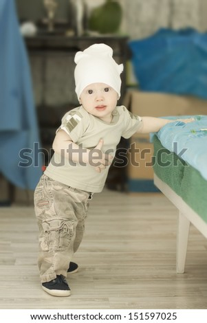 Adorable baby boy trying to stand up - stock photo