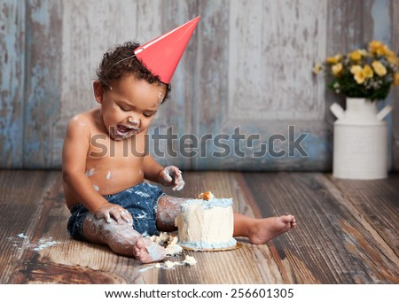 Adorable baby boy wearing a red party hat and eating a small birthday cake. - stock photo