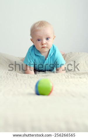Adorable baby boy with a funny face playing with the little ball - stock photo