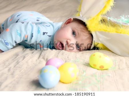 Adorable baby boy with Easter bunny ears and eggs - stock photo
