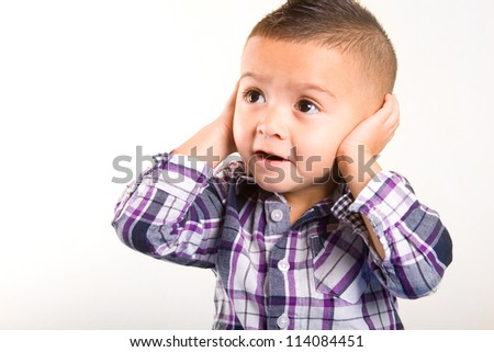 adorable baby boy with his hands closing his ears - stock photo