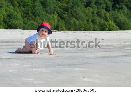 Adorable baby crawling on an untouched beach - stock photo