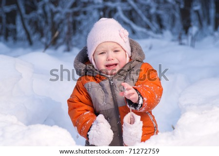 Adorable baby disappointed after eat cold snow in winter forest. Take away one mitten? - stock photo