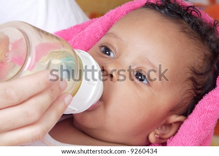 Adorable baby drinking a bottle - focus in the face - - stock photo