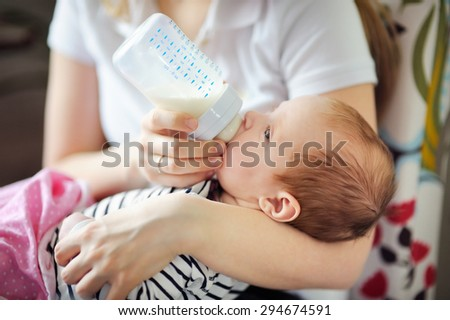 Adorable baby drinking milk from bottle in mother hands