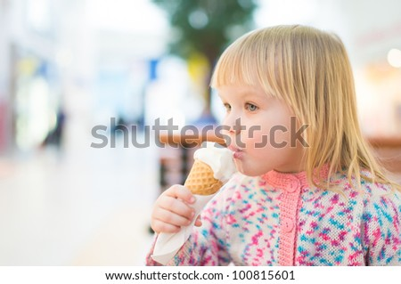 Adorable baby eat ice cream sitting on bench in mall - stock photo