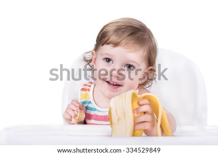 Adorable baby eating banana, healthy food concept