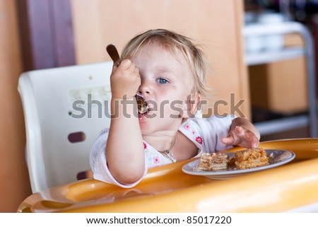 Adorable baby eating cake in a chair with a fork - stock photo