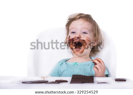 Adorable baby eating chocolate bar for the first time - stock photo