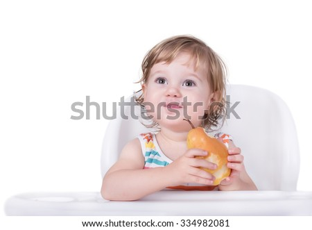Adorable baby eating pear, healthy food concept - stock photo