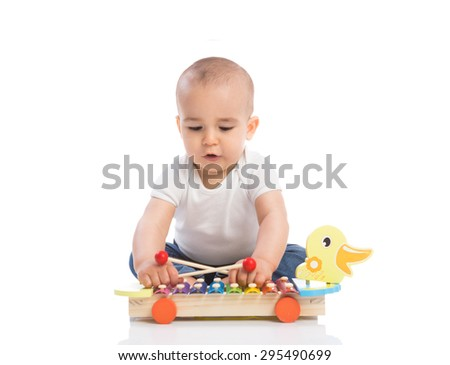 Adorable baby enjoy and playing percussion isolated - stock photo
