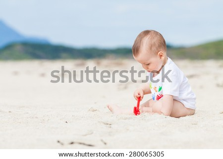 Adorable baby exploring the sand on the beach with a toy shovel with mountains in the background