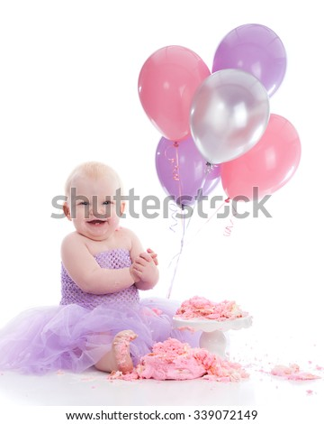 Adorable baby girl eating a birthday cake.  Isolated on white. - stock photo