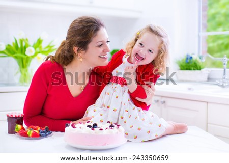 Adorable baby girl enjoying swimming in a pool with her mother, early development class for infants teaching children to swim and dive - stock photo