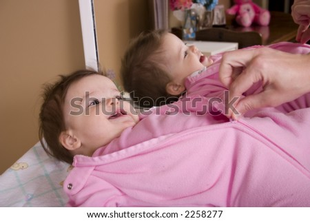 Adorable baby girl getting dressed for bed. - stock photo
