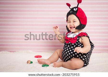 Adorable baby girl in funny ladybug hat and red tutu lying on pink background