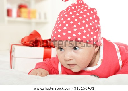 Adorable baby girl in red clothes with gifts - stock photo