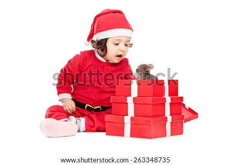 Adorable baby girl in Santa Claus costume opening the Christmas presents and finding a little bunny in one of the boxes, isolated on white background, studio shot - stock photo