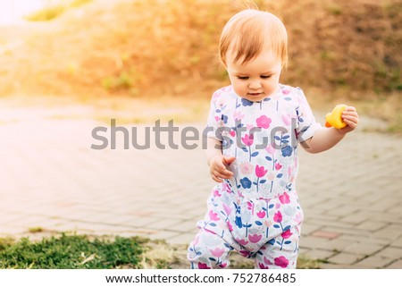 Adorable baby girl in sunlight rays walking in the park with small yellow toy duck