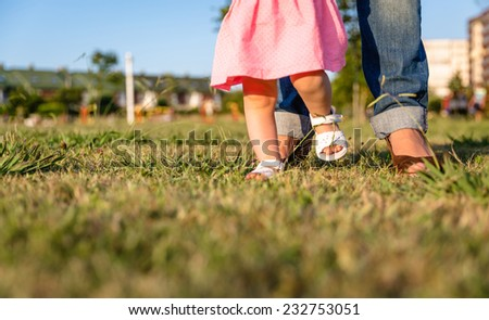Adorable baby girl learning to walk with his mother on the grass park in a sunny summer day - stock photo