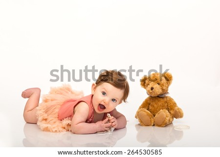 Adorable baby girl lying on belly playing with pearl bracelet near brown teddy bear - stock photo