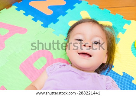 Adorable baby girl lying on floor mats and smiling to camera - stock photo