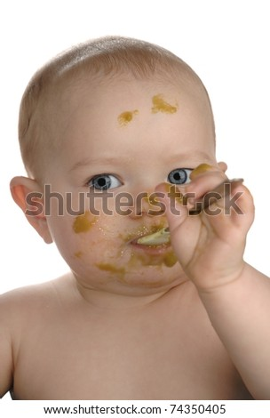 Adorable baby girl making a mess while feeding herself organic green beans, isolated on a white background.