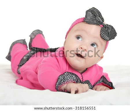 Adorable baby girl on blanket in cute pink clothes on a white background - stock photo
