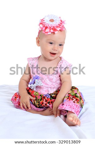 Adorable baby girl on blanket in cute pink clothes on a white background